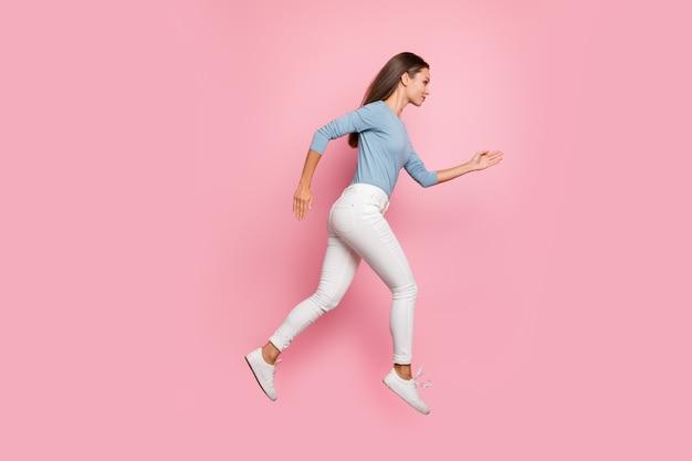 Foto de perfil lateral de corpo inteiro de corpo inteiro de garota confiante focada correndo, saltando para seu objetivo, isolado fundo de cor