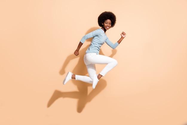 Foto de perfil lateral de corpo inteiro de corpo inteiro de menina ativa de pele escura pulando alto correndo rápido sorrindo isolada em um fundo de cor bege