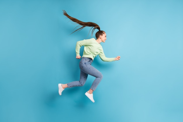 Foto de perfil lateral de tamanho corporal total de garota pulando e correndo apressada com rabo de cavalo de cabelo comprido isolado em um fundo de cor azul brilhante