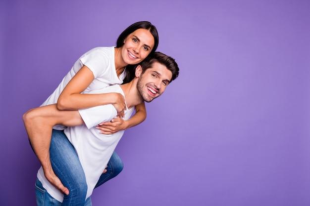 Foto de perfil lateral de um casal adorável de pessoas de cabelos castanhos com um cara carregando uma mulher nas costas com um sorriso dentuço perto de uma camiseta branca vazia isolada fundo de cor violeta pastel