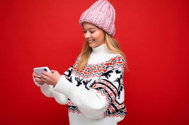 Foto de perfil lateral de uma bela jovem loira sorridente usando um chapéu de malha quente e quente no inverno