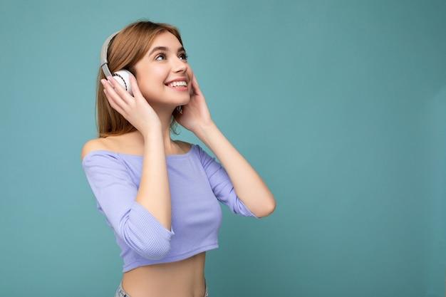 Foto de perfil lateral de uma bela jovem loira sorridente, usando uma blusa cortada azul isolada