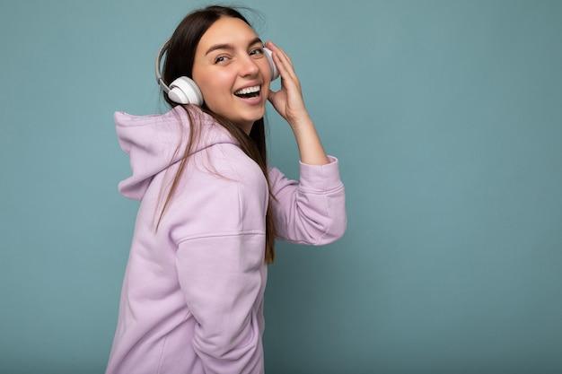 Foto de perfil lateral de uma linda jovem morena sorridente e feliz usando um capuz roxo claro