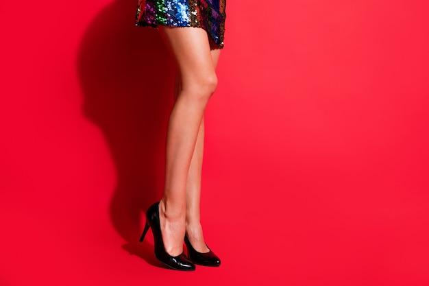 Foto de perfil recortada de uma garota deslumbrante com pernas longas posando com minivestido brilhante sapatos de salto alto isolado fundo de cor vermelha vibrante