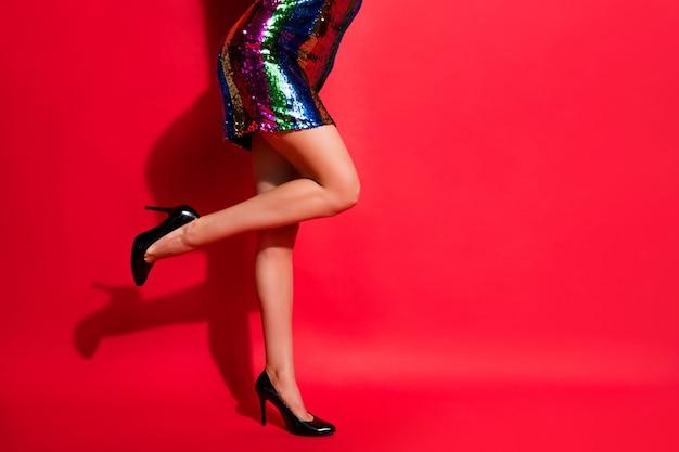 Foto de perfil recortada de uma garota encantadora com pernas longas usando um vestido curto brilhante de salto alto isolado fundo de cor vermelha viva