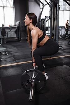 Foto de perfil vertical de mulher atlética com corpo forte e tonificado fazendo exercícios de levantamento terra na academia
