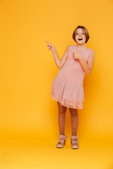 Foto de perna cheia de menina bonita, apontando para o espaço da cópia e sorrindo isolado