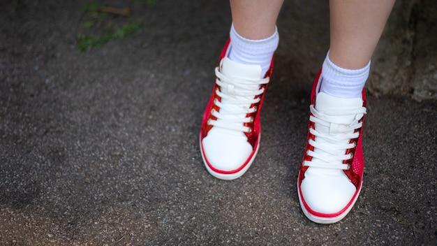 Foto de pernas femininas com tênis vermelho e branco no asfalto cinza molhado