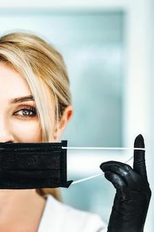 Foto de pertrait da médica em máscara preta e luvas pretas.