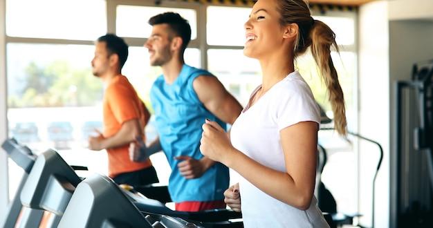 Foto de pessoas fazendo treinamento cardiovascular na esteira na academia