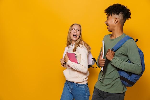 Foto de pessoas positivas, garoto e garota de 16 a 18 anos usando mochilas, sorrindo e segurando cadernos enquanto caminhava, isolada sobre fundo amarelo