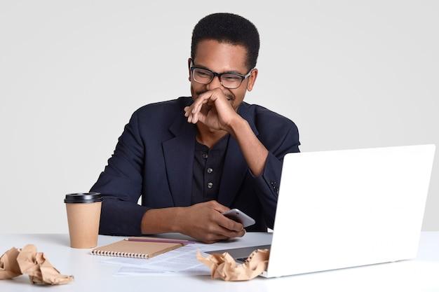 Foto de positivo homem de pele escura, vestido com roupas formais, feliz em ler uma mensagem de texto engraçada, segura telefone celular moderno, usa óculos, cercado por computador portátil, bloco de notas, pedaços de papel