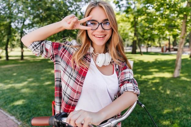Foto de primavera de uma linda garota caucasiana com bicicleta. tiro ao ar livre do modelo feminino elegante em óculos e fones de ouvido.
