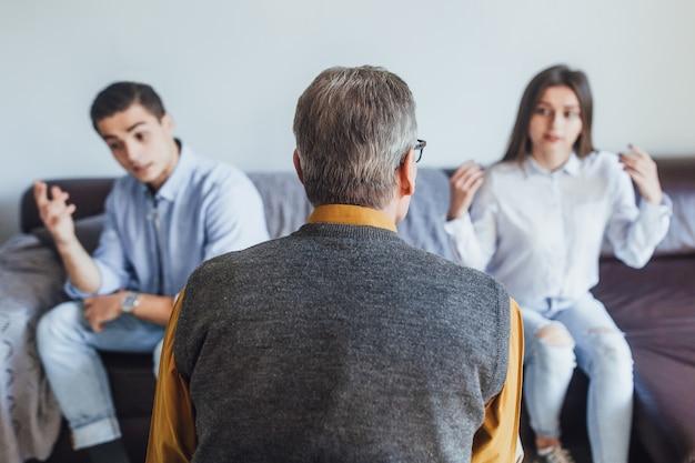 Foto de psicólogo de costas com dois familiares