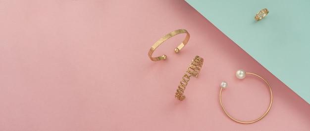 Foto de pulseiras de ouro e anel em fundo de cores pastel com espaço de cópia