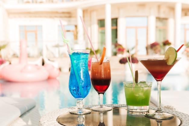 Foto de quatro coquetéis em copos na mesa perto da piscina do hotel, durante um dia ensolarado de verão