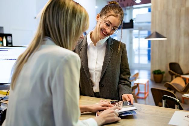 Foto de recepcionista de beleza confiante mostrando os preços de seus serviços a uma cliente na recepção do hotel.