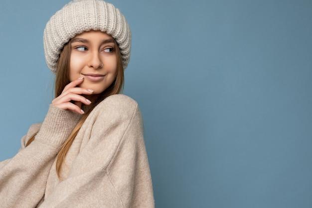 Foto de retrato da bela jovem loira feliz, sorridente, sexy, em pé, isolado na parede de fundo azul, vestindo um suéter bege e um chapéu bege, olhando para o lado e flertando