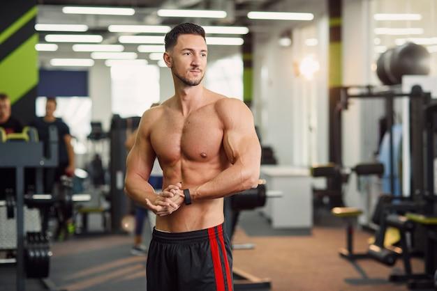 Foto de retrato de cara atraente aptidão com torso nu, fazendo exercícios de aquecimento no ginásio moderno. feche acima do tiro.