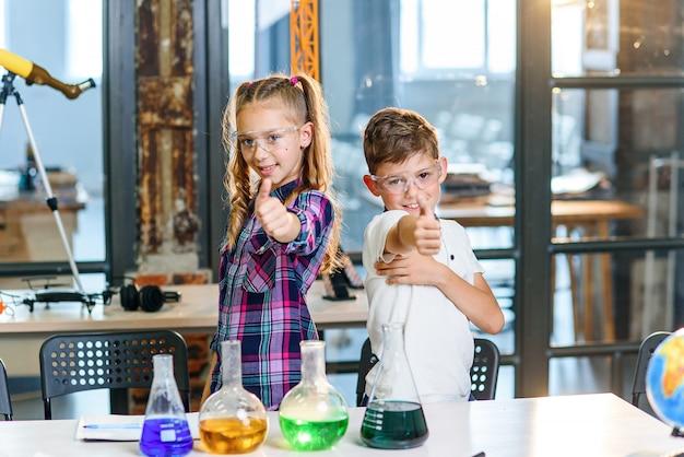 Foto de retrato de duas crianças alegres cientista caucasiano em óculos de segurança, mostrando os polegares na classe química da escola primária