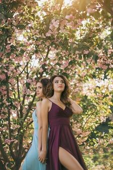 Foto de retrato de moda de duas mulheres perto de árvore florescendo na natureza