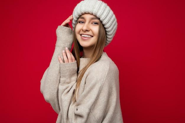 Foto de retrato de sexy fofo atraente feliz sorridente jovem loira escura em pé isolado sobre a parede de fundo vermelho, vestindo uma camisola bege e um chapéu bege, olhando para a câmera. copie o espaço
