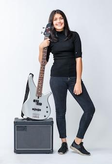 Foto de retrato de um jovem adolescente tailandês-turco atraente em pé e segurando o baixo no amplificador. baixista junior mestiço olhando para a câmera isolada no fundo branco