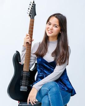 Foto de retrato de um jovem adolescente tailandês-turco sorridente atraente sentado e segurando a guitarra elétrica no amplificador. guitarrista júnior olhando para a câmera isolada no fundo branco