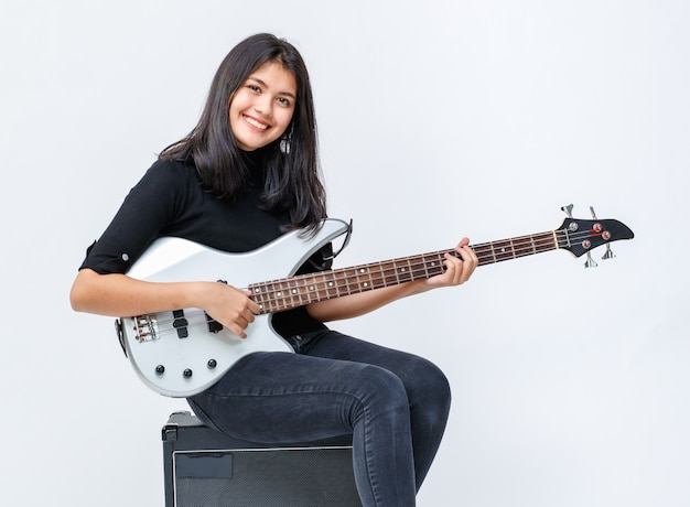 Foto de retrato de um jovem adolescente tailandês-turco sorridente bonito tocando baixo enquanto está sentado no amplificador. guitarrista júnior profissional olhando para a câmera isolada no fundo branco