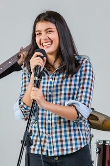Foto de retrato de um lindo sorridente jovem cantor adolescente tailandês-turco cantando uma música com um microfone. o vocalista júnior profissional feliz praticando com a banda com um instrumento ao fundo