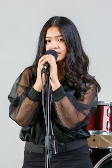 Foto de retrato de uma cantora adolescente cantando uma música com um microfone enquanto olha para a câmera. vocalista de estudante júnior feliz praticando com o instrumento no fundo. conceito de estilo de vida adolescente