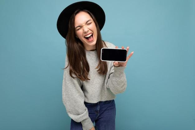 Foto de retrato de uma jovem bonita com chapéu preto e suéter cinza segurando o telefone