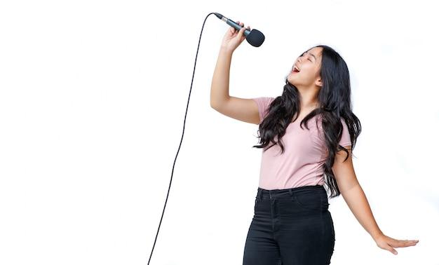 Foto de retrato de uma jovem cantora adolescente cantando uma música com um microfone enquanto olha para a câmera. vocalista de estudante júnior praticando isolado com fundo branco. conceito de ensaio e treinamento