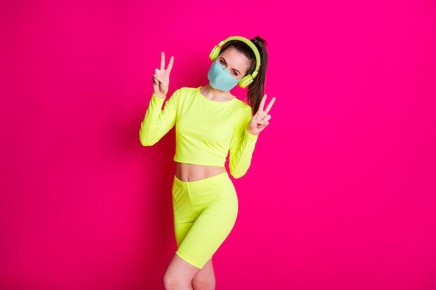 Foto de retrato de uma jovem esportista usando máscara de quarentena de rabo de cavalo esportivo mostrando o sinal de v isolado em um fundo de cor fúcsia brilhante