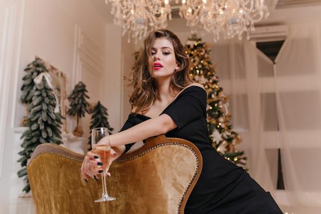 Foto de retrato, mulher gentil e misteriosa com linda manicure e maquiagem brilhante, posando encostada no sofá