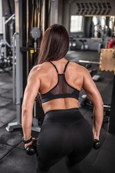 Foto de retrovisor vertical de uma esportista fazendo exercícios de músculos das costas na academia