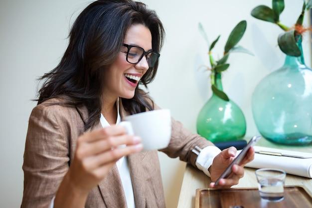 Foto de rindo de mensagens de texto de jovem empresária com seu telefone celular no café.