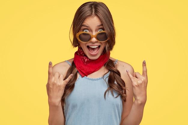 Foto de rosto de uma mulher hippie provocante e descolada mostra gesto de rock n roll com a mão exclamando em voz alta