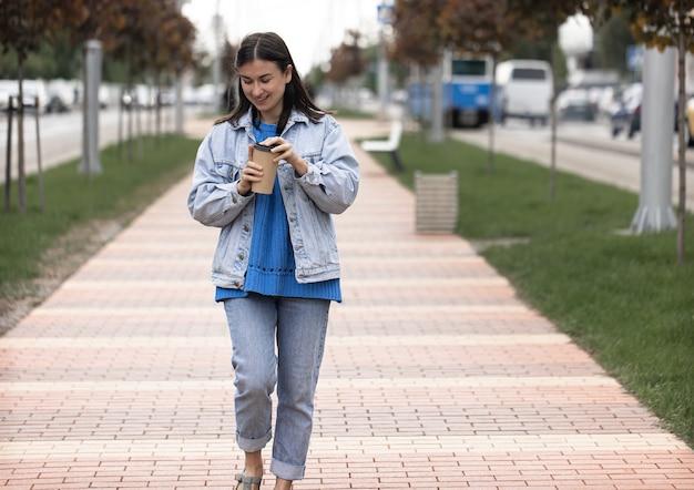 Foto de rua de uma jovem atraente caminhando por uma rua da cidade com um café na mão
