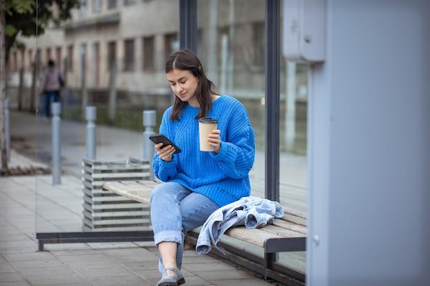 Foto de rua de uma jovem com um telefone na mão e um café para viagem.