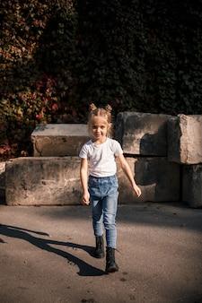 Foto de rua de uma menina linda em jeans e uma camiseta branca em um fundo de lajes de concreto e folhas de outono
