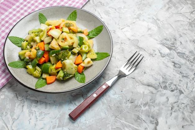 Foto de salada de tomate verde em prato oval, vista inferior, garfo em comida escura