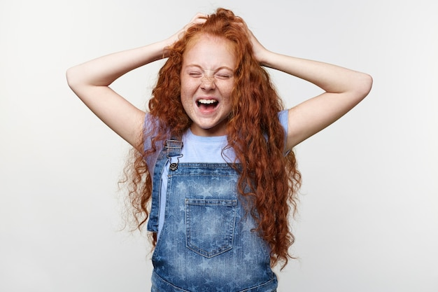Foto de sardas sceaming garotinha com cabelo ruivo, com as mãos levantadas, segurando a cabeça, em pé sobre uma parede branca com olhos fechados e boca aberta, parece infeliz.