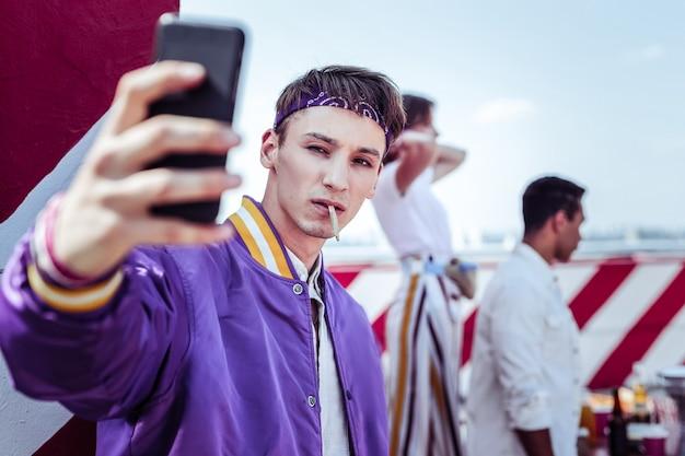 Foto de selfie. aluno sério mantendo o cigarro na boca enquanto posa para a câmera