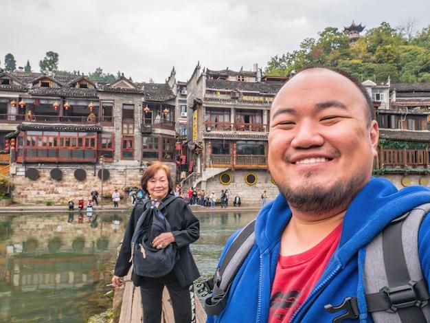 Foto de selfie de um viajante asiático em família com vista panorâmica da cidade velha de fenghuang