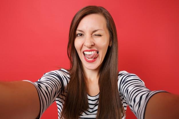 Foto de selfie de uma jovem alegre em roupas listradas casuais piscando, mostrando a língua