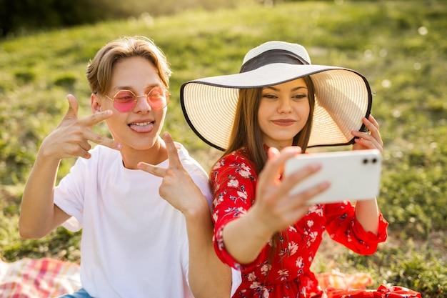 Foto de selfie no telefone de um lindo casal jovem em um parque de verão