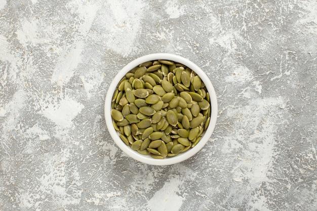 Foto de sementes verdes de abóbora em fundo branco de vista superior