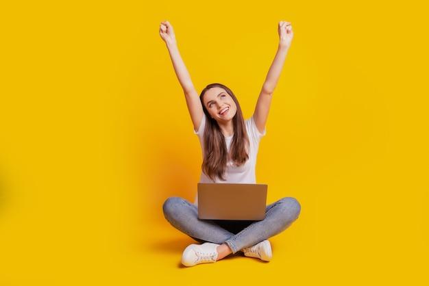 Foto de senhora alegre e atônita segurando laptop olhando para cima e vestindo camiseta branca posando em fundo amarelo