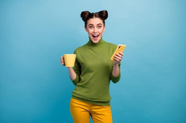Foto de senhora alegre, engraçada, segurar bebida, caneca freelancer, navegar, telefone, boca aberta, boas notícias, usar, verde, gola, calça amarela, isolado, cor azul, parede